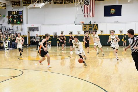 The 2019-2020 Bobwhites, led by Ben Archembault, bring the ball up the court with the stands packed behind them. Photo Credit:  Bobwhite Basketball, Facebook