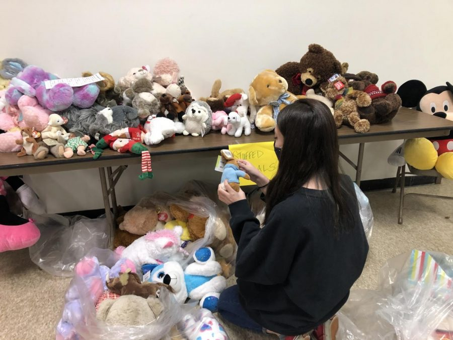 NHS Member Yukina Benjamin ('22) kneels beside a table full of plush toys, selecting the best fit for her assigned family.  Photo credit:  Emily Parent