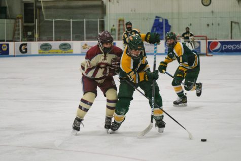 Liam Wood ('23) battles with a Spaulding player for the puck.  Photo credit:  Messenger Photographer Ari Beauregard