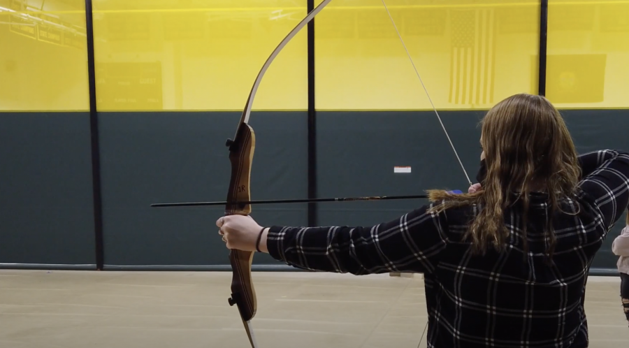 A student practices archery in physical education class.  Photo credit:  Dino Patsouris
