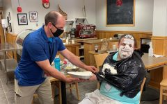 Kieran Kivlehan receives his pie in the face from NCTC teacher Tim Hurteau.  Photo credit:  Lindsay Bernard ('22)